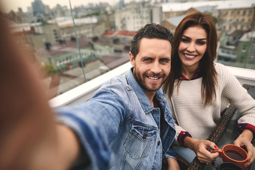 una coppia che si è conosciuta in una chat di incontri si fa una foto sulla terrazza di un caffè