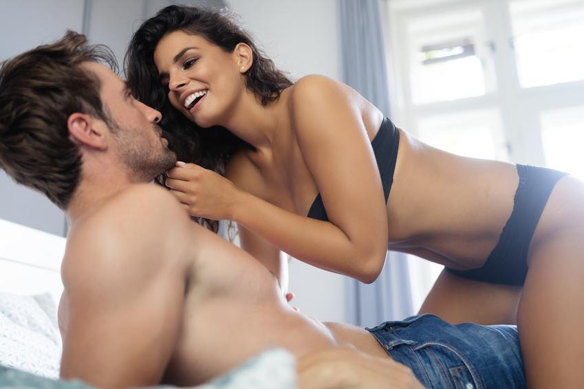 donna in biancheria intima sorride al partner sdraiato sotto di lei all'inizio di un incontro extraconiugale
