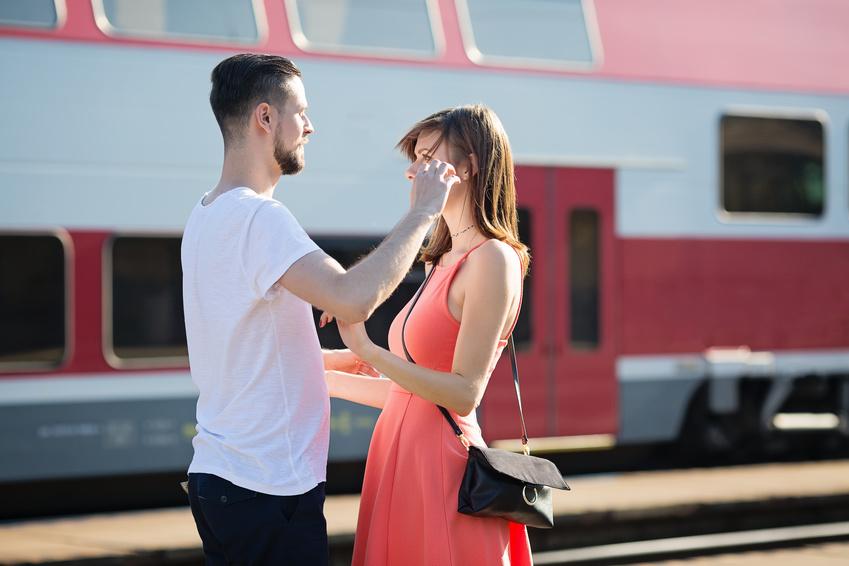 Un uomo saluta la sua ragazza di fronte ad un treno in quanto hanno una relazione a distanza dopo essersi conosciuti su un sito di incontri