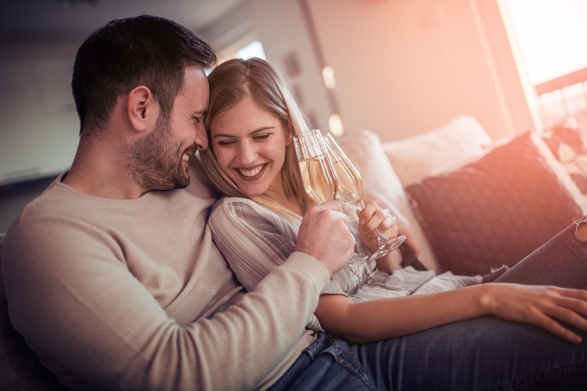 una coppia brinda con dello spumante al loro incontro su una chat di incontri