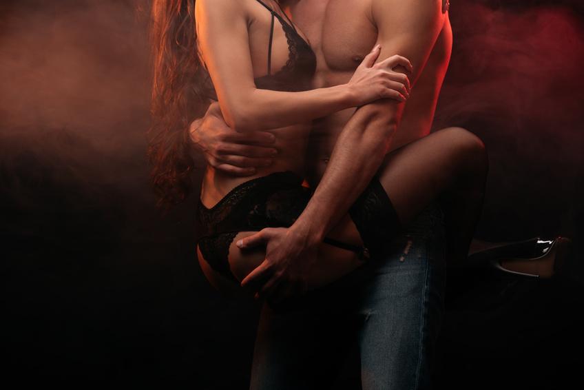 i corpi seminudi di una coppia si abbracciano in piedi nella penombra durante un incontro extraconiugale