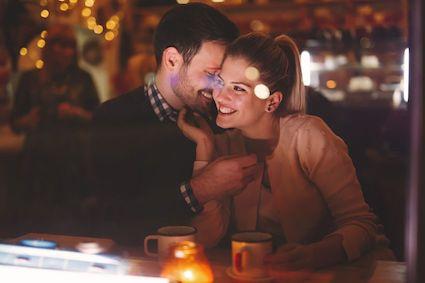 una coppia si incontra per un incontro occasionale elegante e lei, in un abito di pallettes nere, accarezza il viso di lui, in giacca e camicia